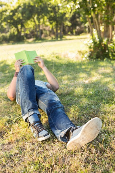 Young man reading book in the park on a summers day