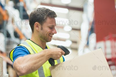 Smiling manual worker scanning package in warehouse