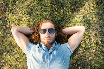 Young man lying down in the park on a summers day