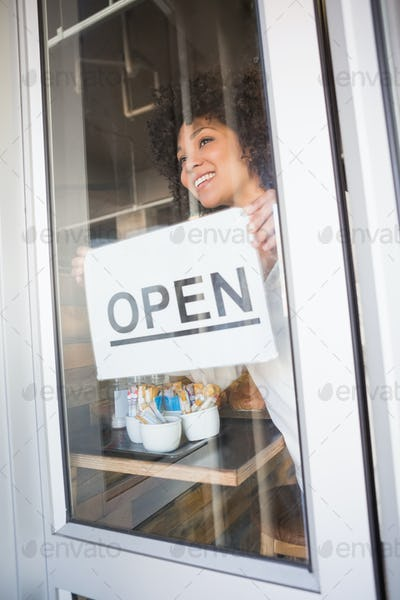 Beautiful worker showing open sign at the bakery