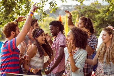 Happy hipsters dancing to the music at a music festival