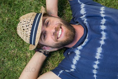 Handsome hipster lying on grass on a summers day