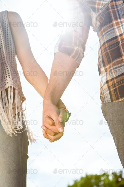 Couple holding hands in park on a summers day