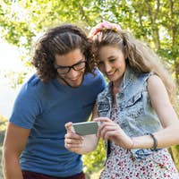 Cute couple looking at their selfie on a summers day