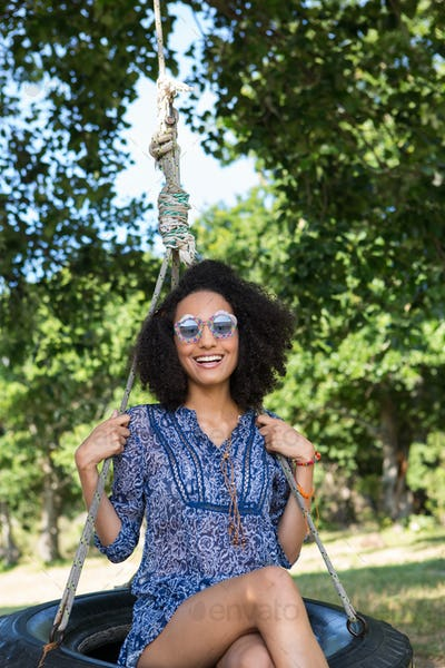Pretty young woman in tire swing on a summers day