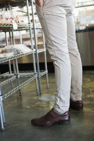 Stylish legs of employee standing at the bakery
