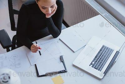 Woman analyzing chart of work progress and planning