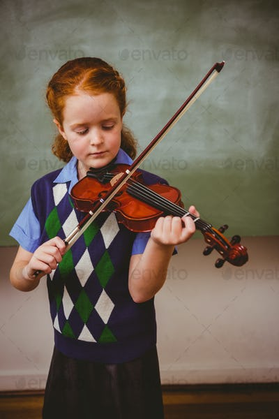 Portrait of cute little girl playing violin in the classroom