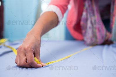 Mid section of female fashion designer at work