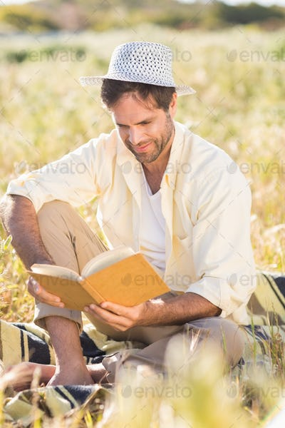 Happy man reading a book on a sunny day