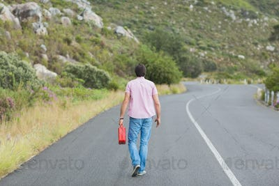 Man walking away holding petrolcan at the side of the road
