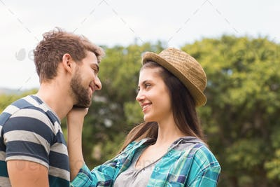Young couple smiling at each other on a sunny day
