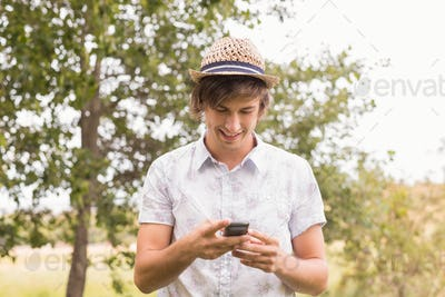 Happy young man using smartphone on a sunny day