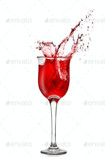 splash of red wine in goblet isolated on white