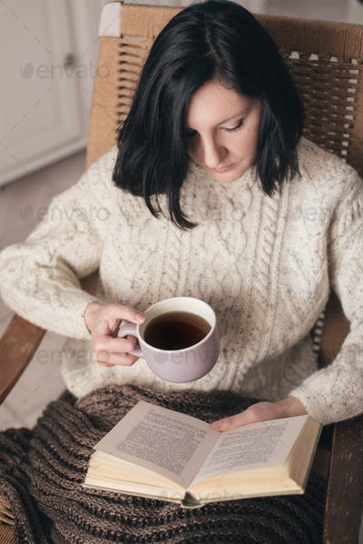 Woman reading book and drinking tea