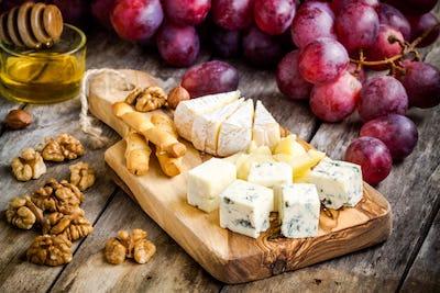 Cheese plate: Camembert, Parmesan, blue cheese, bread sticks, walnuts, hazelnuts, honey, grapes
