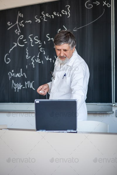Senior chemistry professor writing on the board while having a c