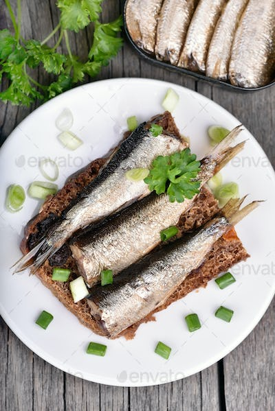 Sandwich with sprats on wooden table
