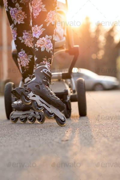 Woman Rollerblading While Pushing Baby Stroller