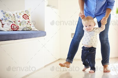 Mother Helping Young Son As He Learns To Walk