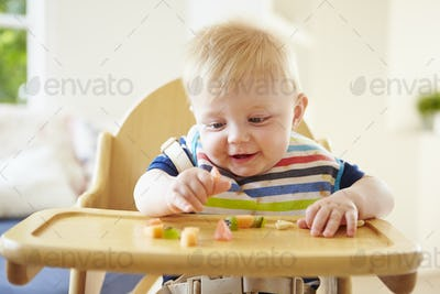 Baby Boy Eating Fruit In High Chair