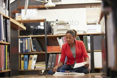Businesswoman Sitting On Office Floor Reading Documents