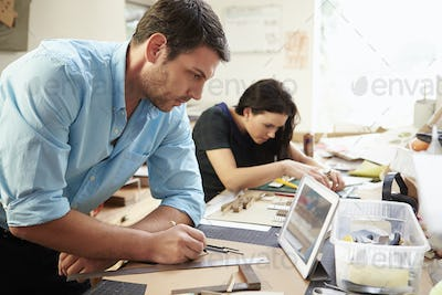 Two Architects Making Models In Office Using Digital Tablet