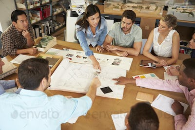 Female Boss Leading Meeting Of Architects Sitting At Table