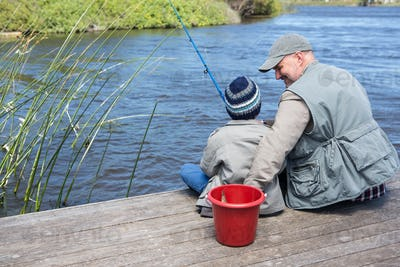 Father and son fishing at a lake in the countryside