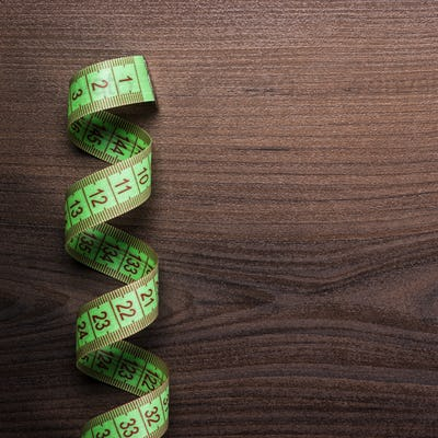 Green Measuring Tape Over Wooden Background