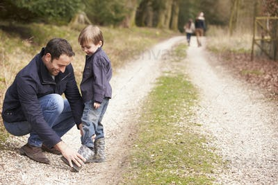 Father Helping Son To Put On Shoe During Family Walk