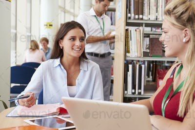 Two Female College Students Studying In Library Together