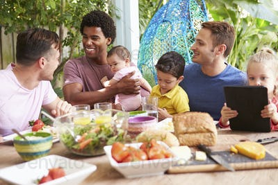 Group Of Fathers With Children Enjoying Outdoor Meal At Home