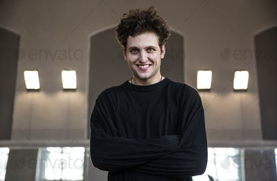 Portrait of a smiling young man with arms folded