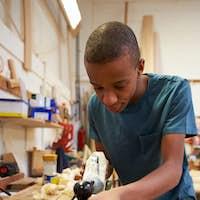 Apprentice Planing Wood In Carpentry Workshop