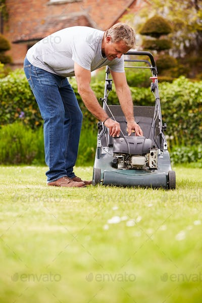 Man Working In Garden Cutting Grass With Lawn Mower