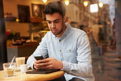 Man Viewed Through Window Of Caf' Using Mobile Phone