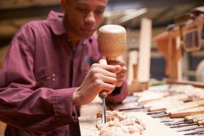 Apprentice Using Chisel To Carve Wood In Workshop