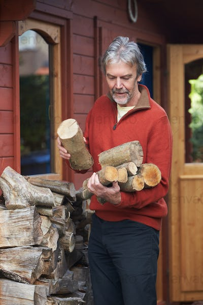 Mature Man Collecting Logs For Fire From Woodpile In Garden