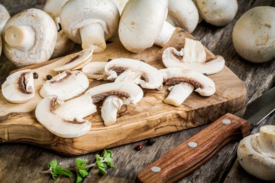 raw sliced mushrooms on a wooden cutting board