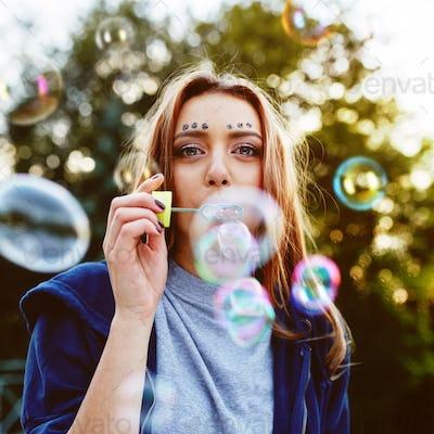 Young woman portrait blowing soap bubbles