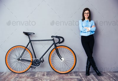 Cheerful young businesswoman standing near bicycle