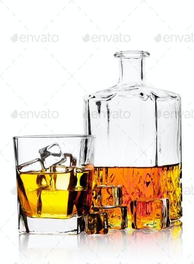 Glass of whiskey with ice and decanter