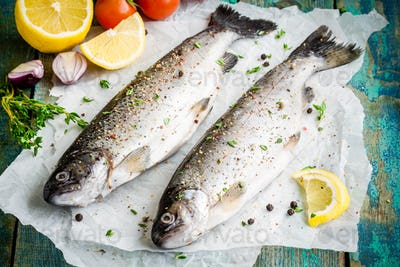 two raw trouts on paper with thyme and lemon