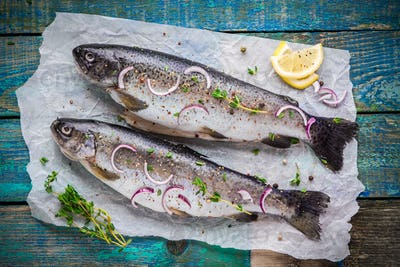 two raw trouts on paper with thyme and lemon and red onion slices