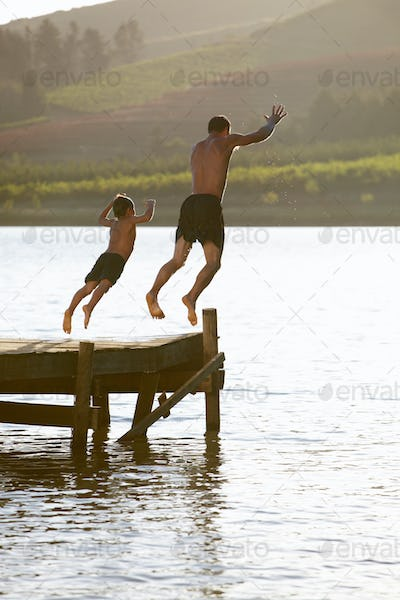 Young man with child jumping to water