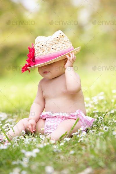 Baby Girl In Summer Dress Sitting In Field Wearing Straw Hat