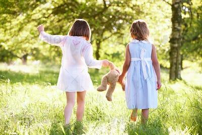 Two Young Girls Walking Through Summer Field Carrying Teddy Bear