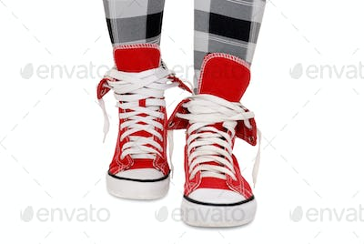 Red sneakers, checkered leggings. Isolated over white.