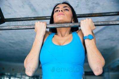 Beautiful woman working out on horizontal bar